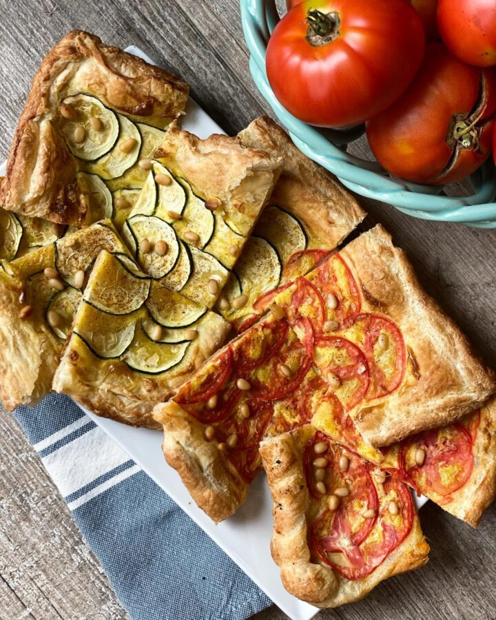 ZUCCHINI and tomato TART, rectangle pieces of tart piled on a white platter. Some tarts are made with tomatoes and some zucchinis.