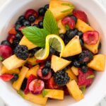 Fruit Salad in a round bowl with pineapple, cherries, blueberries and blackberries