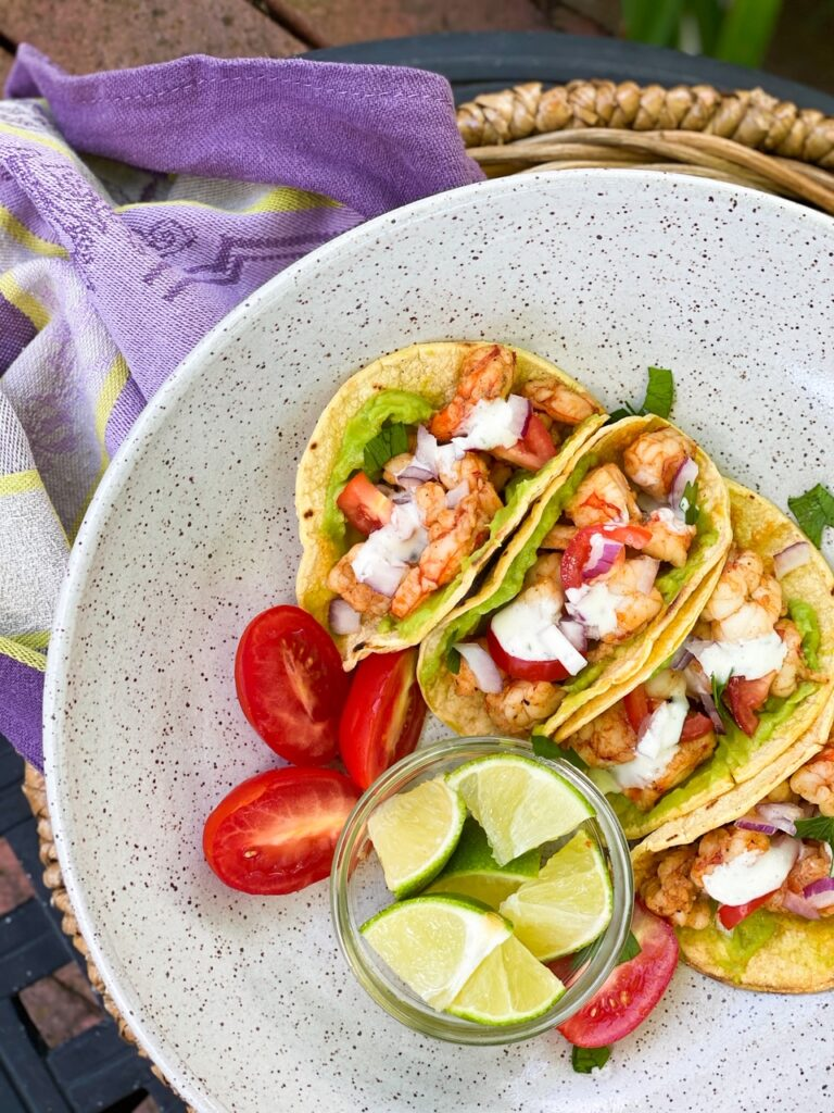 SHRIMP STREET TACOS in a corn shell on a plate with a side of lime