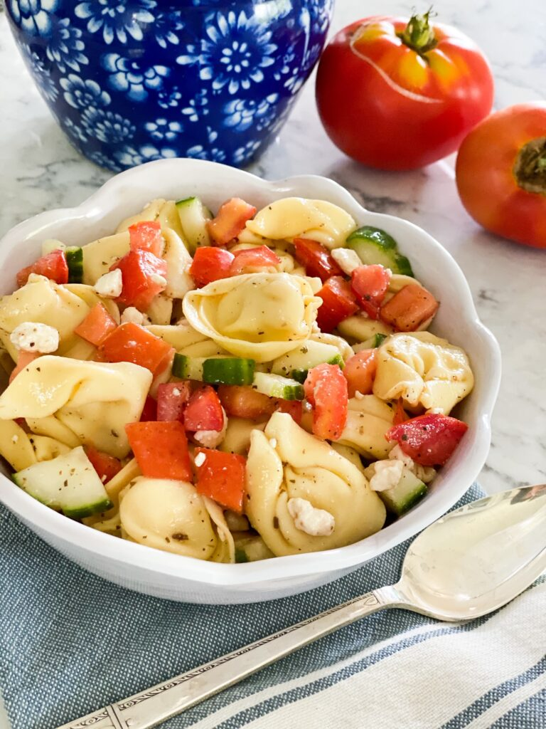 Round bowl full to the top with TORTELLINI PASTA, tomatoes, cucumbers and feta cheese.