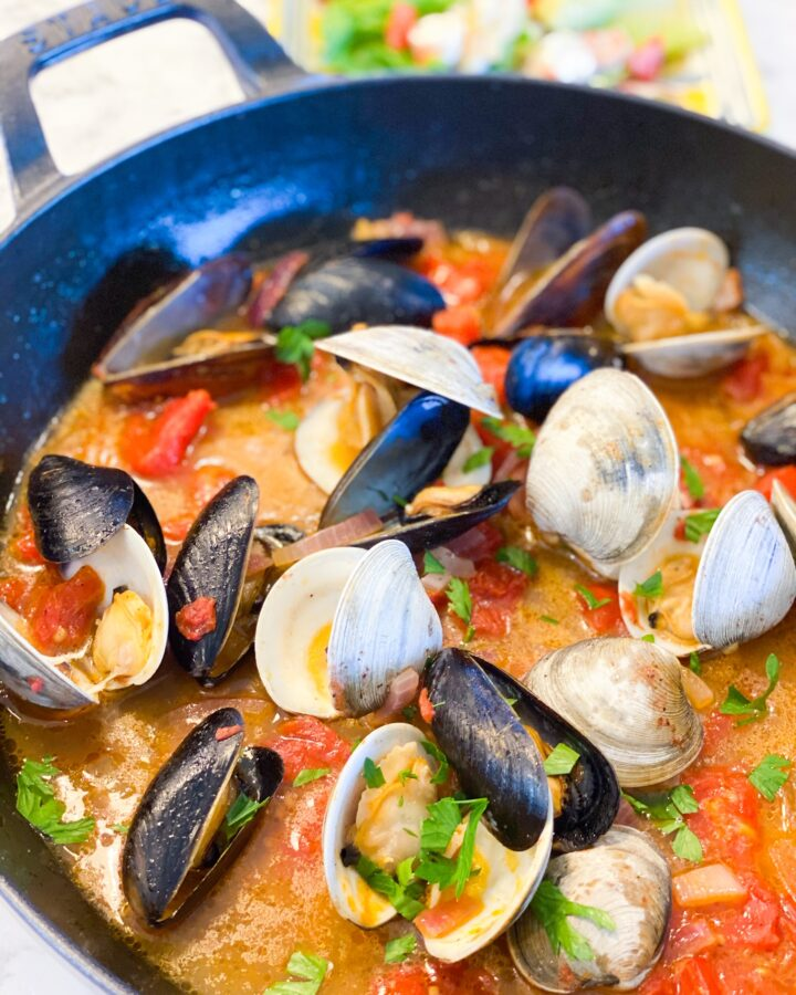 CLAMS-AND-MUSCLES in a staub skillet with tomatoes and red onions. Garnished with fresh parsley.