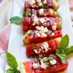GRILLED-WATERMELON spears on a white rectangle platter with feta and balsamic vinegar on top and garnished with fresh basil.