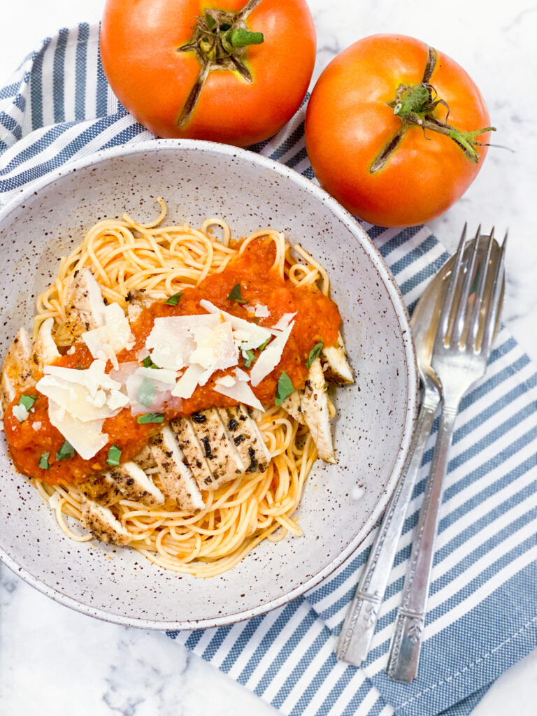 Pomodoro Sauce over grilled chicken that's on top of the angel hair pasta. Parm cheese is sprinkled on top.