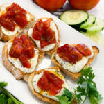 Toasted bread topped with the ricotta cheese spread and roasted tomatoes.