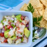 SHRIMP-CEVICHE in a square bowl with silver spoon and a side of tortilla chips.