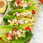 SHRIMP-CEVICHE loaded in to romaine LETTUCE-BOATS. Lettuce boats are lined up on a colorful rectangle platter.