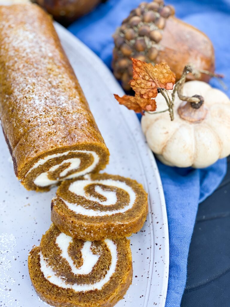 Grandmothers Pumpkin Roll on a gray platter with 2 slices cut and displayed