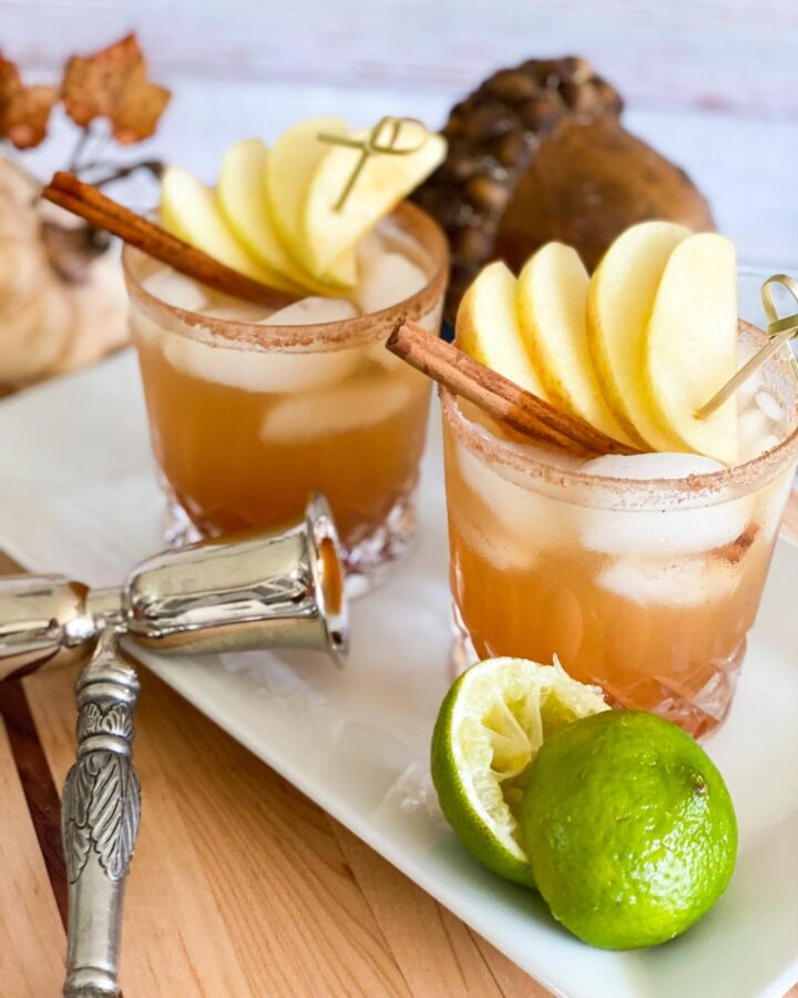 Two glasses of APPLE PIE MARGARITA. Light brown liquid the color of cinnamon is garnished with apples and cinnamon stick and a cinnamon sugar rim