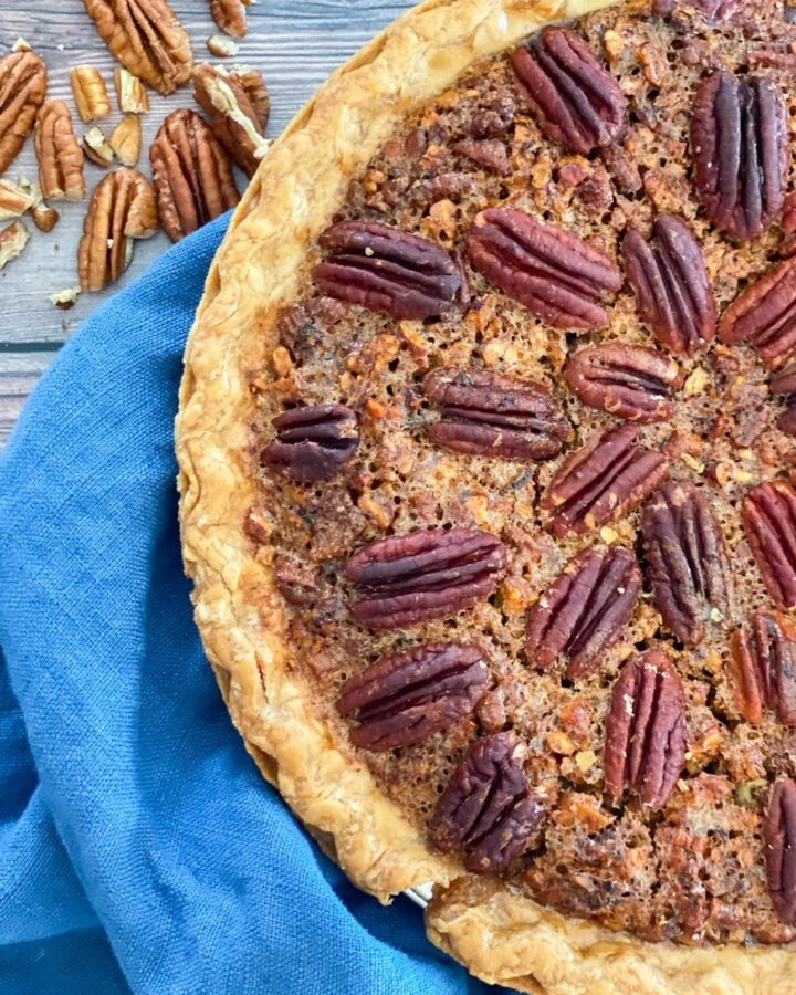 Pecan Pie in a pie plate sitting on a blue towel