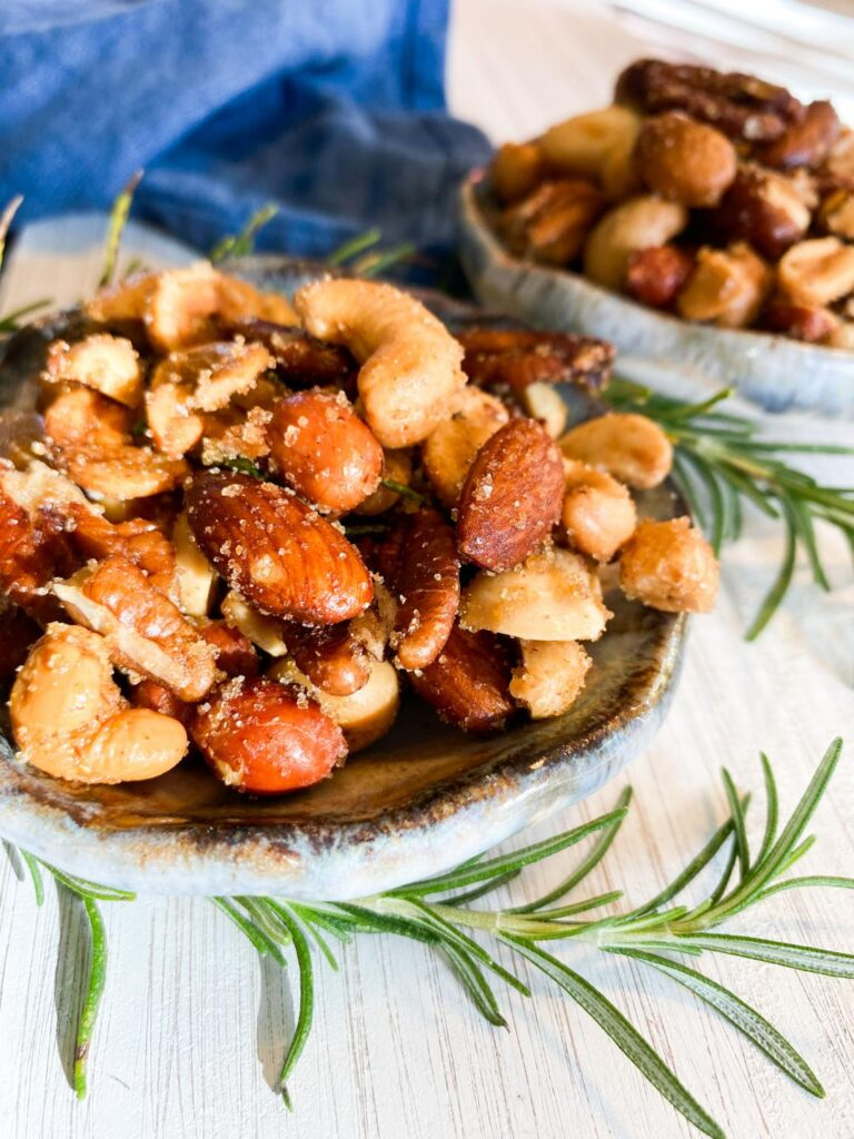 Mixed nuts in small blue bowls on a white tray garnished with fresh rosemary