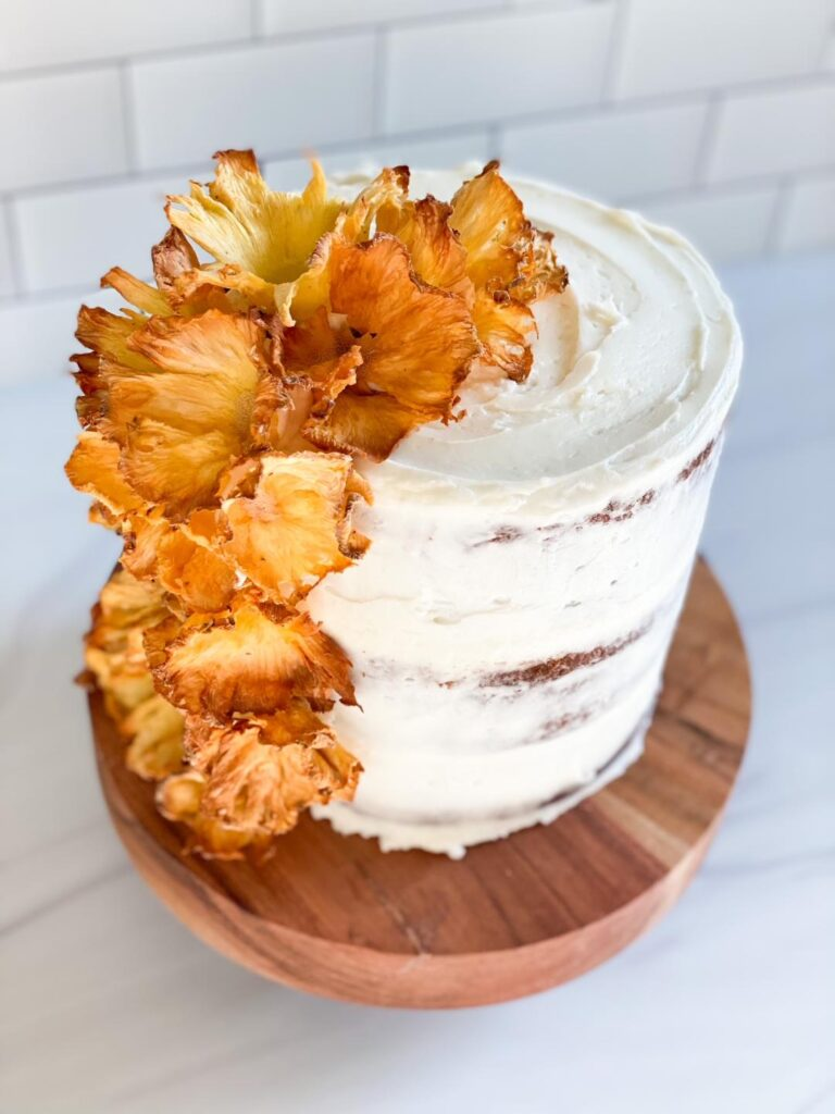 hummingbird cake with white icing and yellow flowers made from dried pineapples
