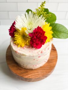 3 layer cake with white icing topped with pink and yellow carnations.